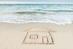 House drawn on sand by sea Stock Photography