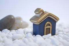 House dream. House miniature standing  on white pebbles Home concept Royalty Free Stock Image
