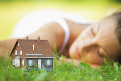 House of dreams. Young woman on a lawn dreaming of her new home Stock Photography