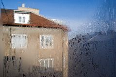 House dreamy. Town house viewed through window pale,abstract paintings made by frost on glass Stock Image