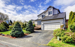 House drive way and curb appeal. Siding house with garage. Green lawn with trimmed hedges, flourishing bushes and fir trees Royalty Free Stock Photography