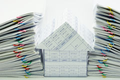 House between dual pile overload document. With colorful paperclip on white background royalty free stock photos