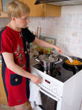 House efforts. The woman cooks  food on a cooker Royalty Free Stock Photo