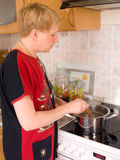 House efforts. The woman cooks  food on a cooker Stock Photo