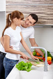 House efforts. The young girl with the young man cuts vegetables on kitchen Stock Photo