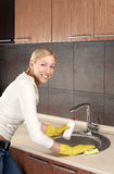 House efforts. The smiling blonde washes ware in a bowl on kitchen Stock Photos