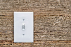 House Electric Light Switch in ON Position on Wood. Traditional North American toggle white house electric light switch in ON position on aged old wood wall stock photo