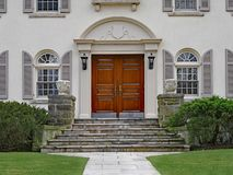 House with elegant double wooden front door. Stucco house with elegant double wooden front door and stone steps royalty free stock photo