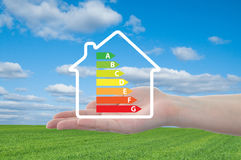 House and energy efficiency graph on hand. Blue sky and meadow in background stock photos
