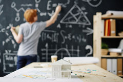 House Engineering Student. House model and floor plans on desk against background of young architect writing formulas on blackboard stock images