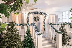 House entrance decorated for holidays. Christmas decoration. garland of fir tree branches and lights on the railing Stock Image