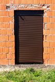House entrance doors completely closed with new dark brown rollup window blinds mounted on unfinished red brick wall stock images