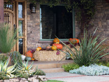 House entrance Hallowene deco. Stone stairs and Halloween pumpkins with hay bales flowers and green shrubs Royalty Free Stock Photos