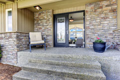 House entrance porch with stone wall trim. View of house entrance porch with stone wall trim and black glass door Royalty Free Stock Photo