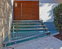 House entrance with stairs over a small pool Royalty Free Stock Image