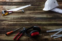 House equipment for building, maintenance, woodworking and repairing. With hard hat, architect blue print, safety ear protection and DIY tools over rustic wood royalty free stock image