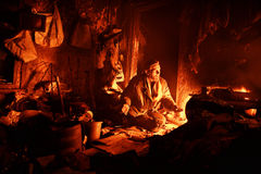 The house of the eremite. The poor man sits at night at the furnace Royalty Free Stock Photo