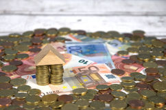 House on euro banknotes and coins. Expressing the concept of mortgage stock photography