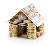 House of Euro money. House made from European coins with banknote for roof, isolated on white background Stock Photos