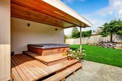 House exterior. Backyard deck with jacuzzi. House exterior with walkout deck and jacuzzi stock photo