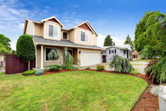 House exterior with beautiful curb appeal. Green lawn with brown sawdust and decorative trees Royalty Free Stock Photography
