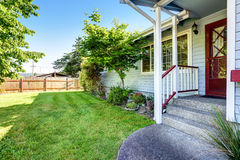 House exterior with blue siding trim, red front door with porch. Well kept lawn. Northwest, USA stock photos
