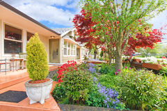 House exterior with curb appeal. VIew of entrance porch with beautiful flower bed and trees Stock Photos