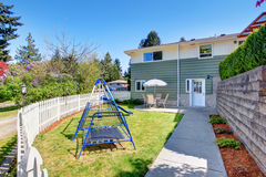 House exterior. Fenced back yard with patio area and kids playground Stock Image