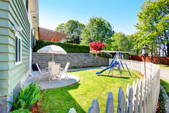 House exterior. Fenced back yard with patio area and kids playground Royalty Free Stock Photos