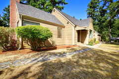 House exterior. Front yard with dry grass and concrete tile walk Royalty Free Stock Photography