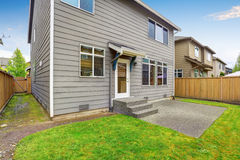 House exterior with mocha siding. View of patio area with concrete floor. Royalty Free Stock Photo