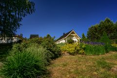 House exterior on a sunny day with a clear and blue sky. House exterior on a sunny day with a clear and blue sky with flower and other greenery stock image
