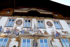 House facade with eight finetsre and drawings of a local party scene in Oberammergau in Germany. Photo made in Oberammergau in Bavaria (Germany). The picture royalty free stock image