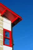House facade with red roof and window against blue sky Stock Photo