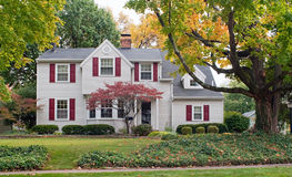 House in Fall with Red Shutters. Large, luxurious house with red shutters and colorful fall foliage Royalty Free Stock Images