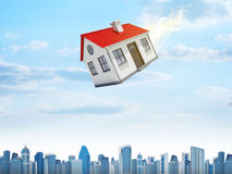 House is falling from the sky. City on background Royalty Free Stock Image