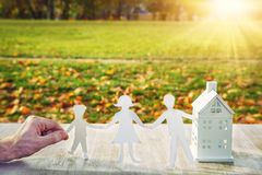 House family concept. Hand holds paper family and house against green park.  Royalty Free Stock Photo