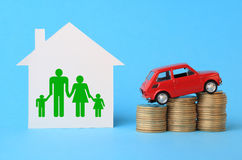 House with family symbol, miniature car and coins Stock Photography