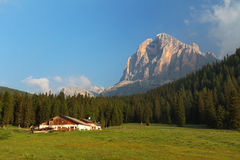 House farm with green forest and Tofane peak, Dolomites Alps Stock Photos