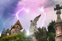 The house of fear. An enigmatic house under the storm and lightnings. Close to the house, the statue of an angel seems to be looking at it Stock Image