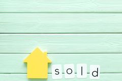 House figure and sold copy on office desk mint green wooden background top view mock-up. Buy house concept. House figure and sold copy on office desk mint green royalty free stock photos