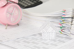 House on finance account with blur old pink alarm clock. House on finance account have blur old pink alarm clock with calculator and pile overload paperwork of Stock Photo