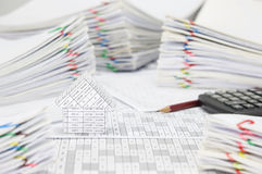 House on finance account have blur brown pencil with calculator. And pile overload paperwork of report and receipt with colorful paperclip place as background stock images