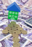 House Finance uk. A house sitting on a pile of money, with a pen and calculator to symbolize house finance in the U.k Stock Images
