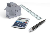 House financing. Concept of house financing with calculator, pen, ruler and silver model of house made of jigsaw pieces Royalty Free Stock Photography