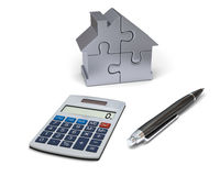 House financing. Concept of house financing with calculator, pen and silver model of house made of jigsaw pieces Royalty Free Stock Photos