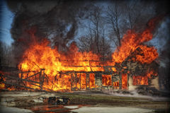 House Fire. Massive fire consuming a house with the American flag waiving from a fire engine royalty free stock images