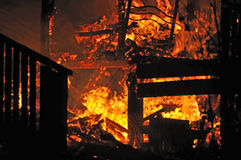 House on fire. Stairs and bedroom furniture silhouetted in house fire Stock Images