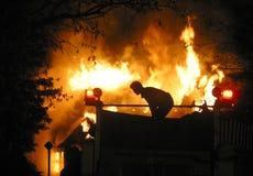 House fire. An Edmonton,Alberta firefighter stands atop a pumper at a blazing house fire Stock Photos