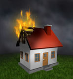 House Fire. And burning home insurance symbol with a burnt damaged residential structure that shows the destruction in flames  and the importance of  smoke Stock Photo